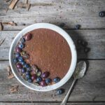 A bowl of chocolate chia pudding with fruit on a wooden table.