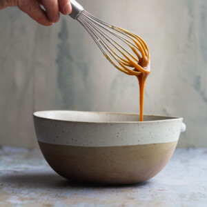Caramel sauce dripping from a whisk in to a bowl.
