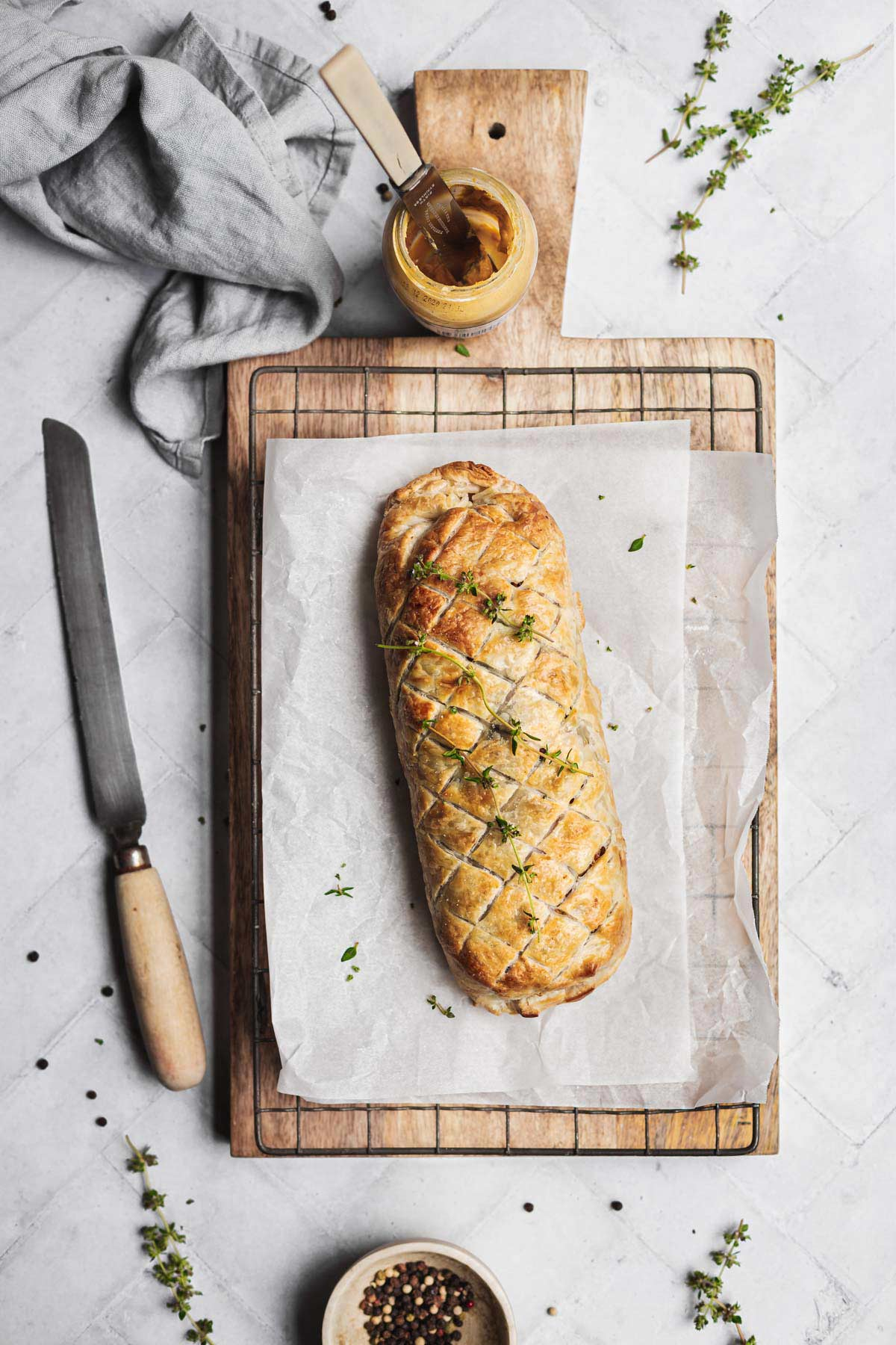 An uncut filled pastry roll on a cutting board on a table setting.