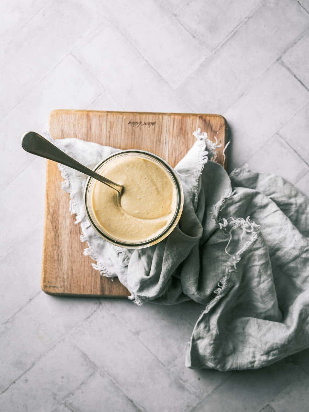 A jar of nut butter on a wooden board with a spoon.
