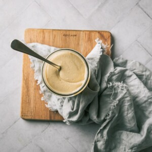 A jar of cashew butter on a wooden board with a spoon.