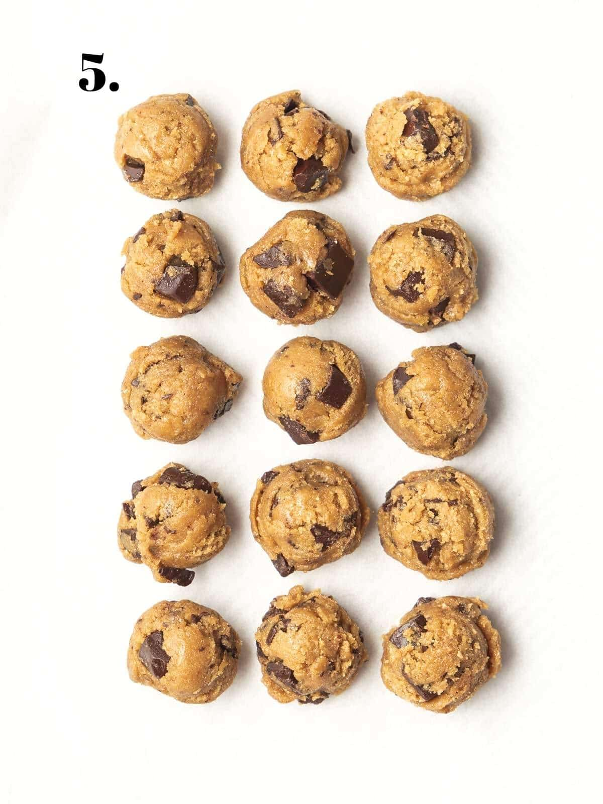 Cookie dough balls on a lined tray.