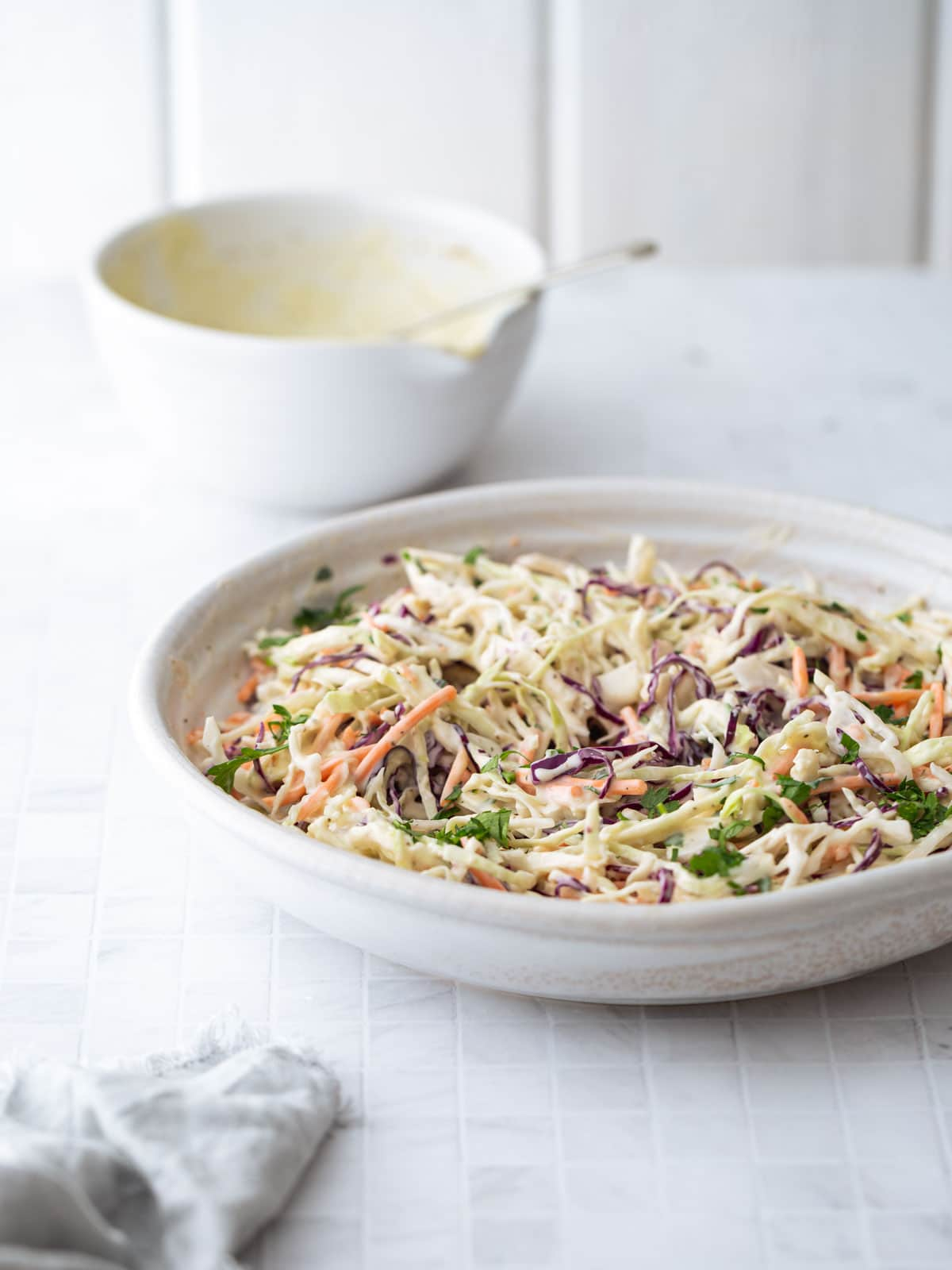 A table setting with a large bowl of shredded salad.
