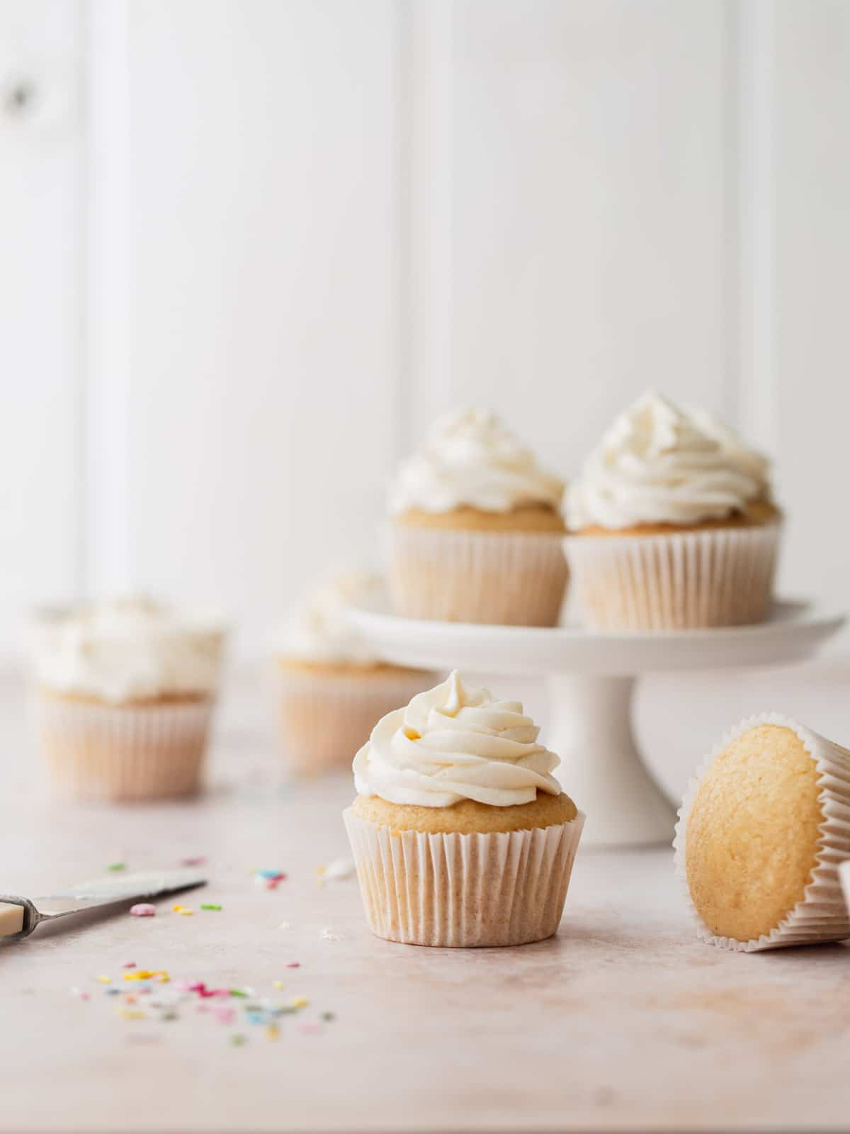 Frosted vanilla cupcakes on a white background.