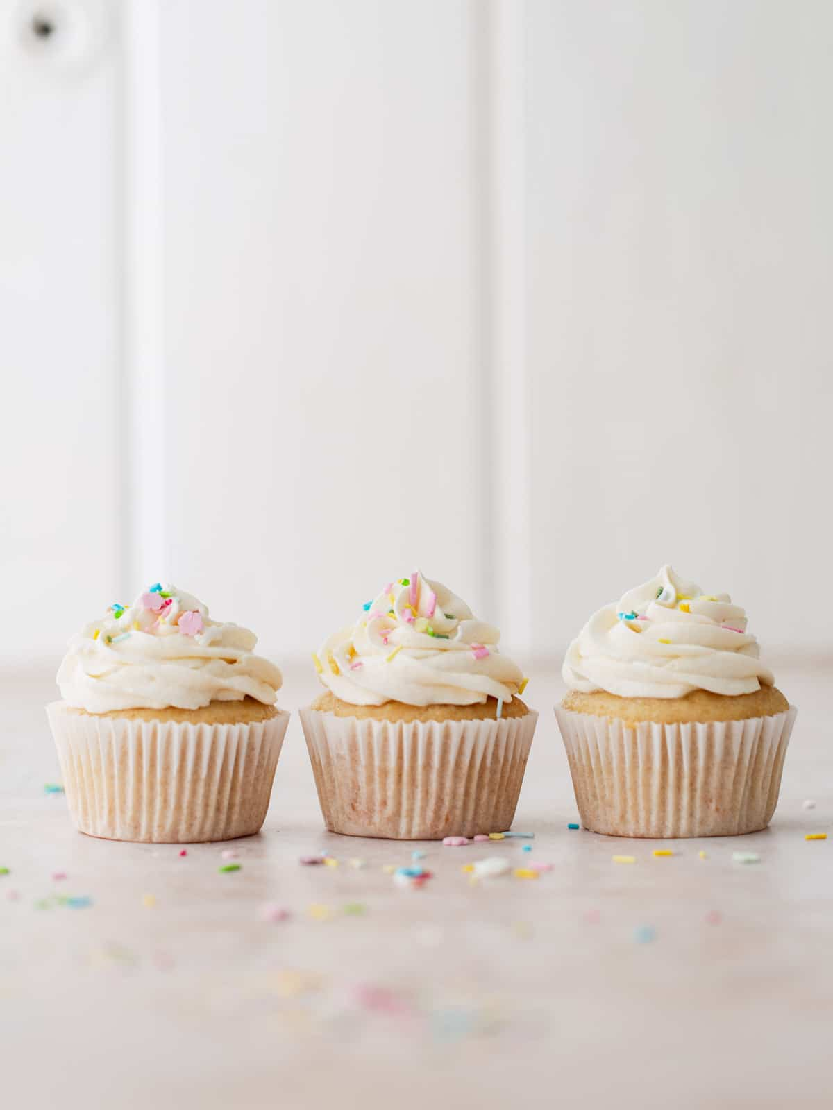 Three frosted vanilla cupcakes with sprinkles.