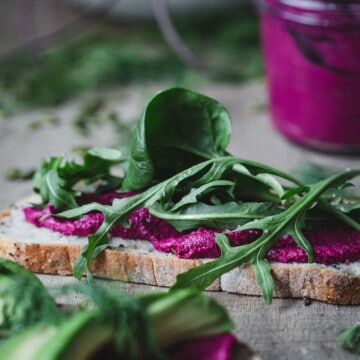 A slice of bread with beetroot hummus and greens.