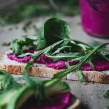 Beetroot hummus on bread with greens on a wooden board.