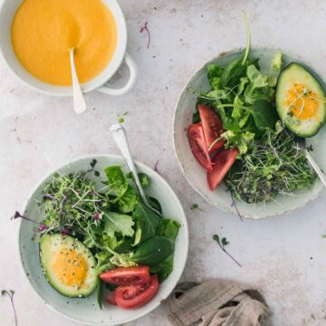 Bowl of green salad with a bowl of carrot salad dressing.