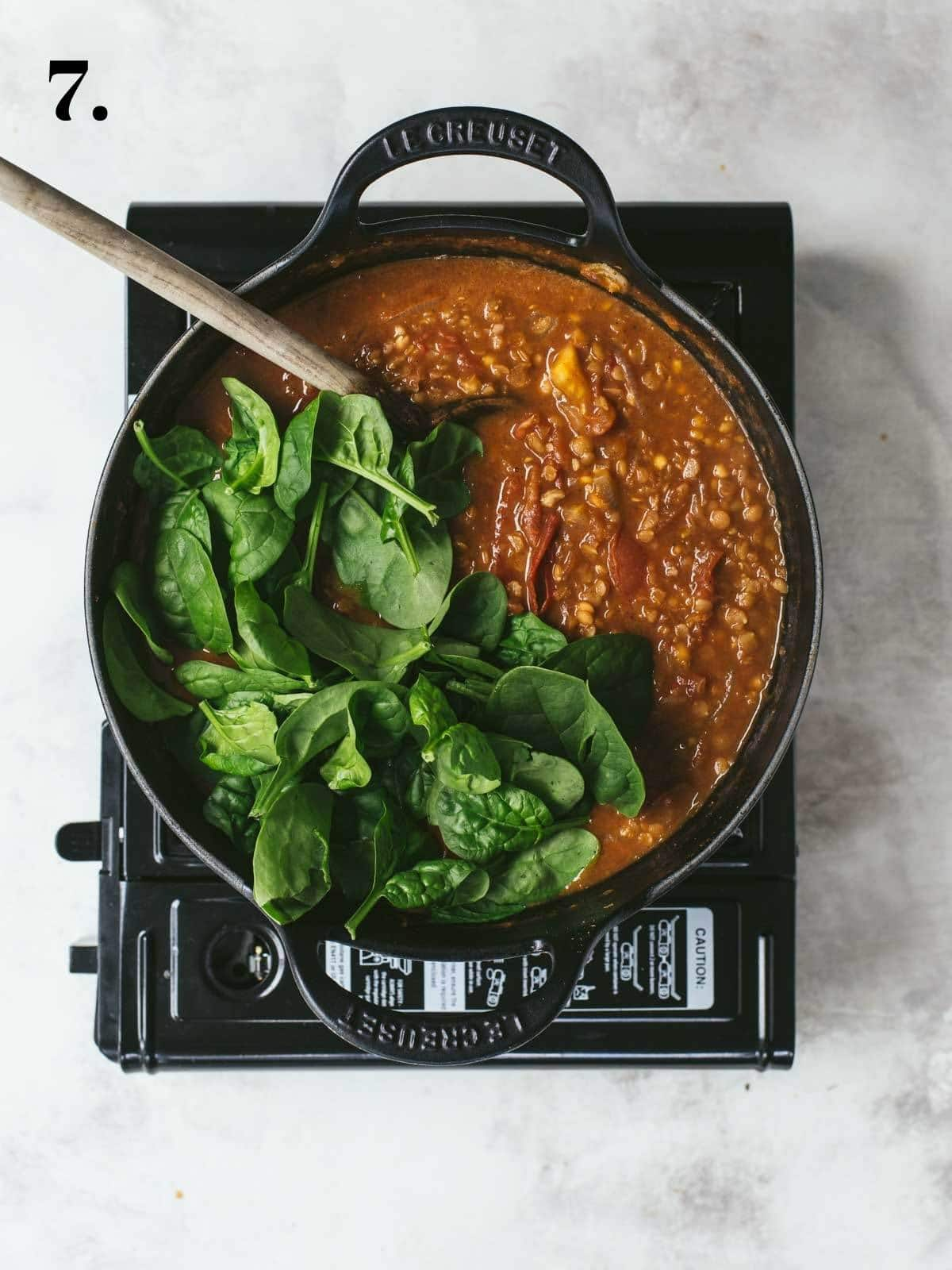 Fresh spinach added to a lentil curry in a pan.