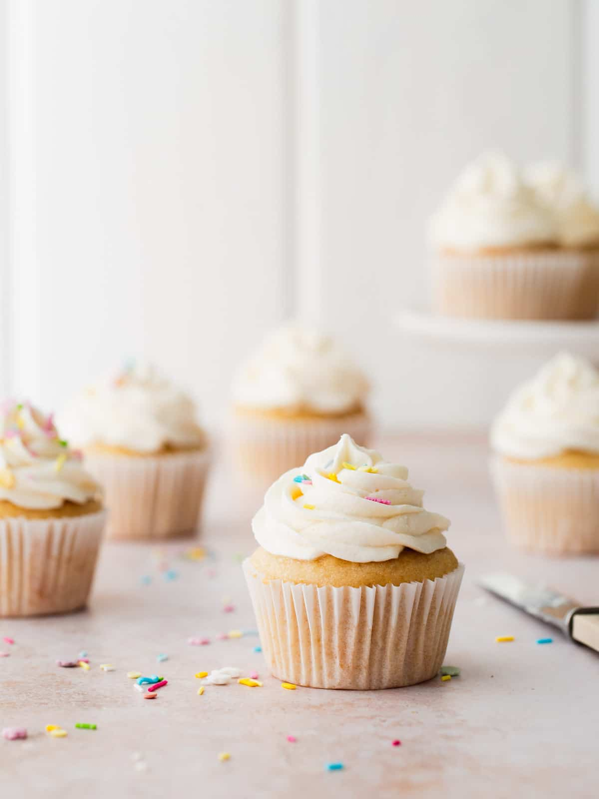 Vanilla cupcakes on a white wooden background.