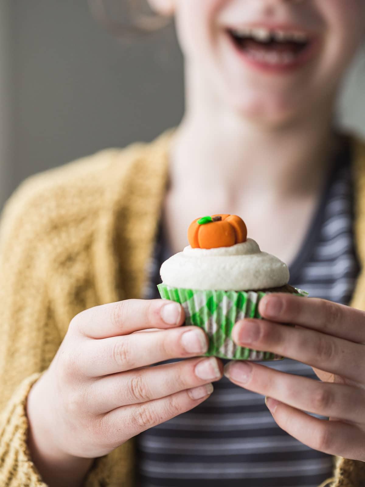 A little girl holding a pumpkin cupcake.