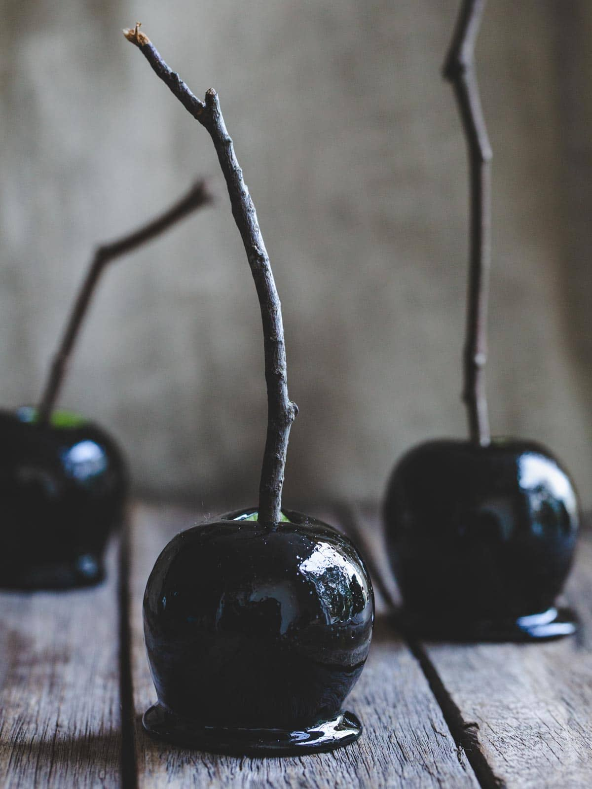 Black candy apples on a wooden table.