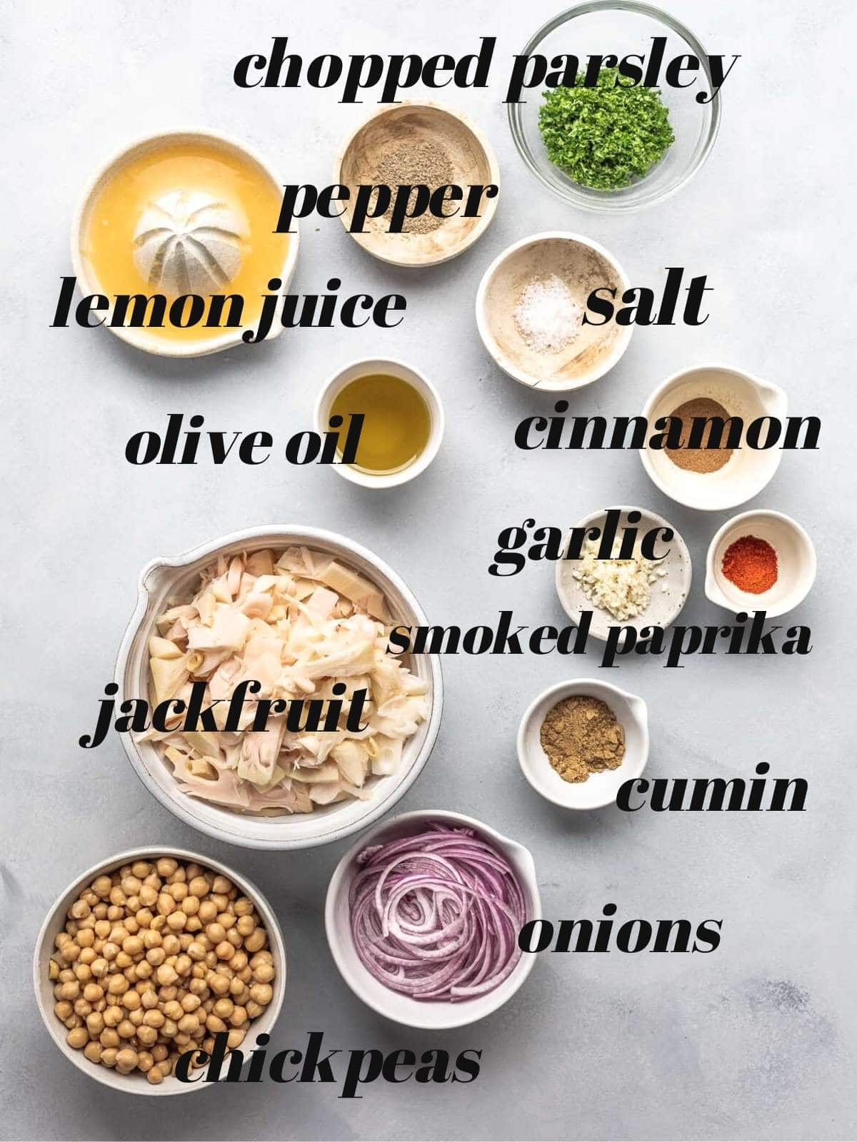 Labelled ingredients in bowls on a grey surface.